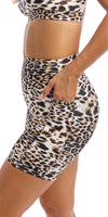 Girl putting hand in side pocket of brown & white cheetah print midi shorts with pockets & matching momentum bra