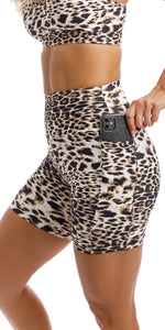 Girl putting phone in side pocket of brown & white cheetah print midi shorts  with pockets & matching momentum bra