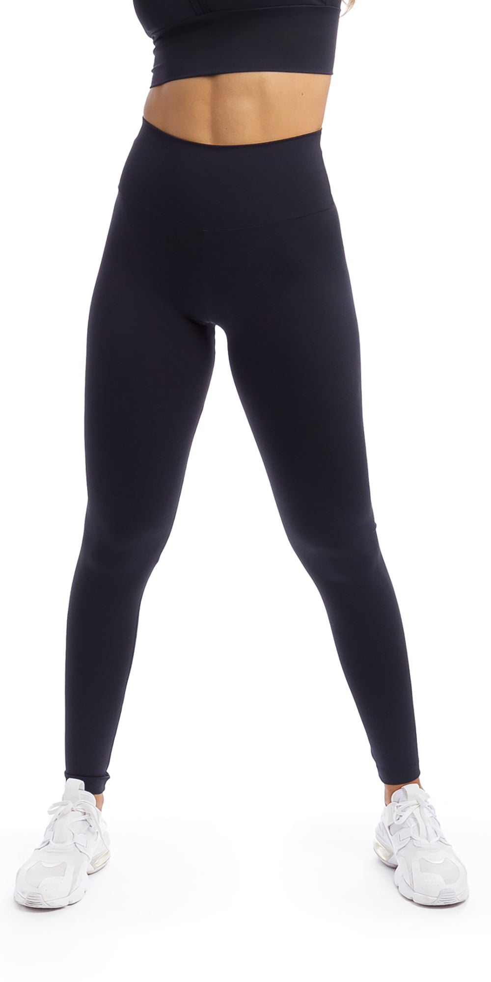Girl wearing midnight body luxe ultra high waist leggings & matching racer bra