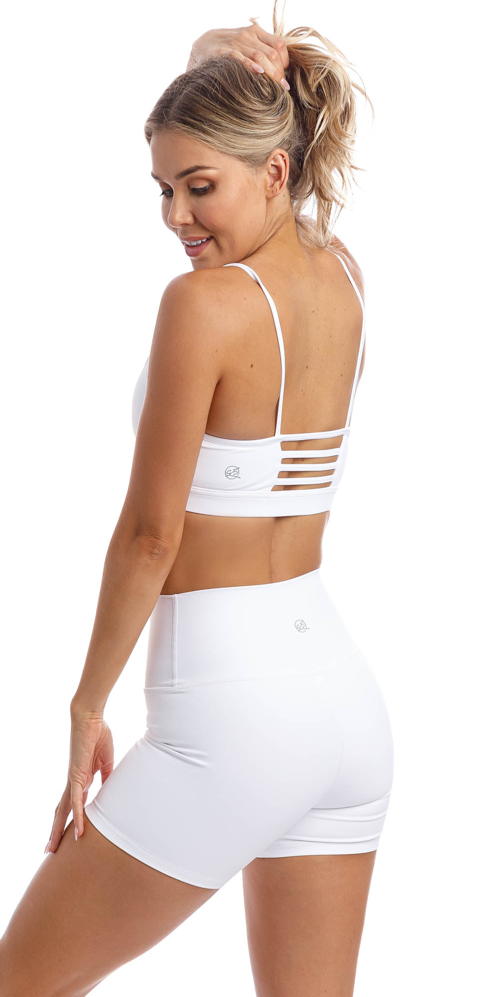 Rear view of girl wearing white momentum bra with three horizontal back straps & matching white lined midi shorts