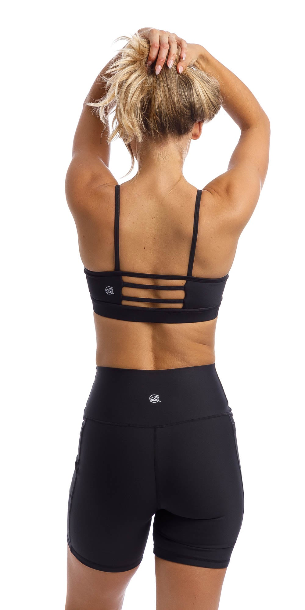Girl wearing midnight momentum bra with three horizontal back straps & matching lined midi shorts