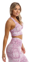 Side view of girl wearing pink and white snake print racer back bra & matching ultra high waist leggings