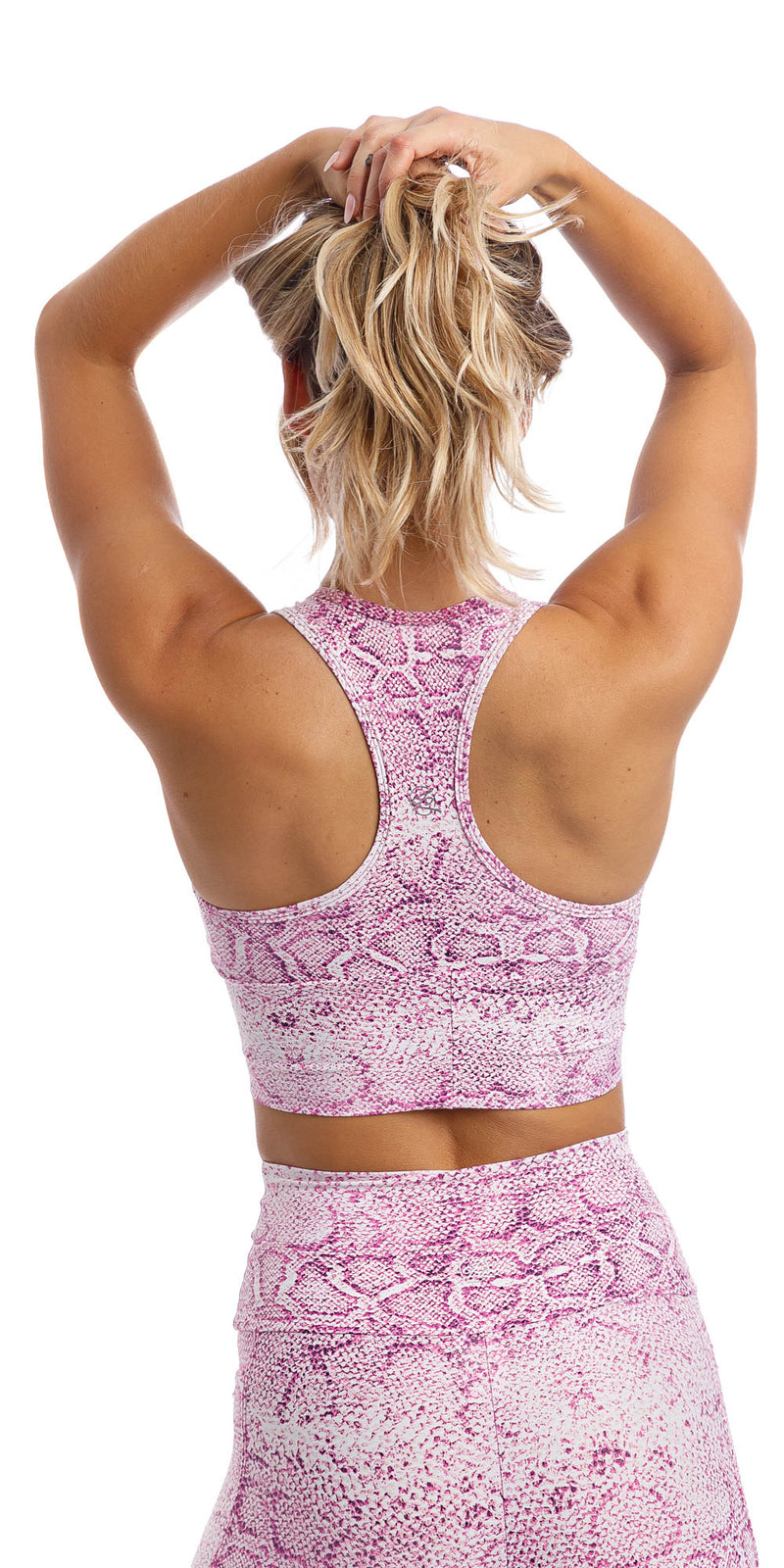 Rear view of girl wearing pink and white snake print racer back bra & matching ultra high waist leggings