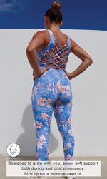 Rear View: Pregnant lady in sleeveless blue, white and pink hibiscus flower print unitard with crisscross back detailing