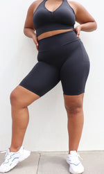 Girl wearing midnight body contouring 2.0 biker shorts with pockets & matching racer back bra