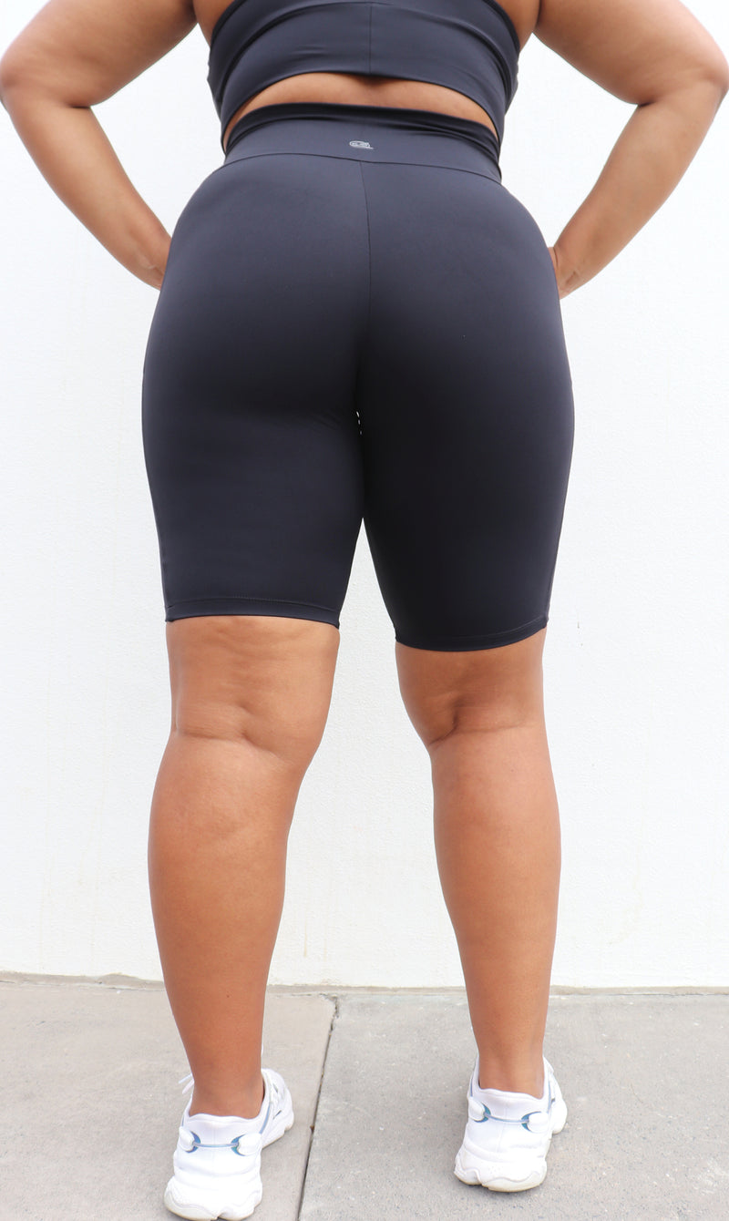Rear View: Girl wearing midnight body contouring 2.0 biker shorts with pockets & matching racer back bra