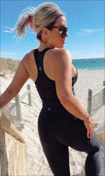 Rear View: Lady on beach wearing midnight body luxe racer back bra & matching ultra high waist leggings