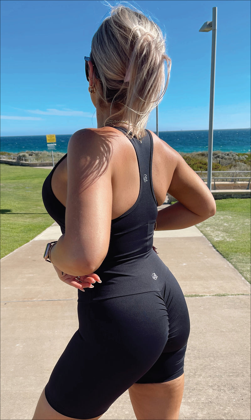 Rear View: Lady on beach wearing midnight body luxe racer back bra & matching ultra high waist scrunch bum midi shorts