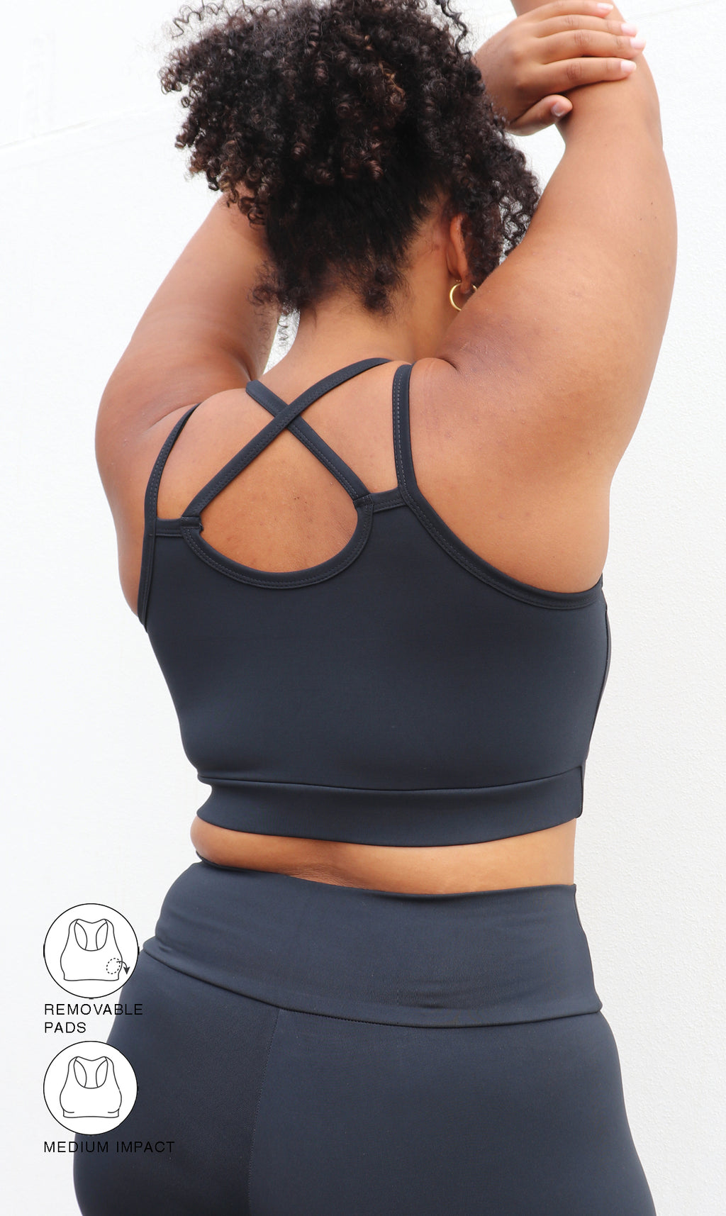 Girl in midnight curvy contouring bra with cross over back strap with hands over head