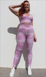 Front View: Lady wearing pink and white snake print ultra high waist leggings & matching racer back bra