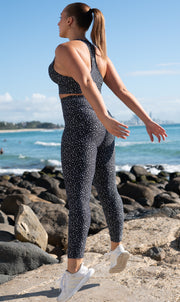 Side view: Girl on beach mid jump, in black and white speckled high waist scrunch bum leggings and matching bra