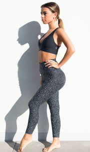 Girl against white wall, pointing her toe, in black and white speckled high waist scrunch bum leggings and black bra