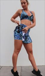 Lady putting phone in side pocket of blue & black tropical palm print skort with pockets & matching infinity bra