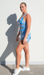 Girl in blue, white & pink hibiscus print racer back bra & matching shorts