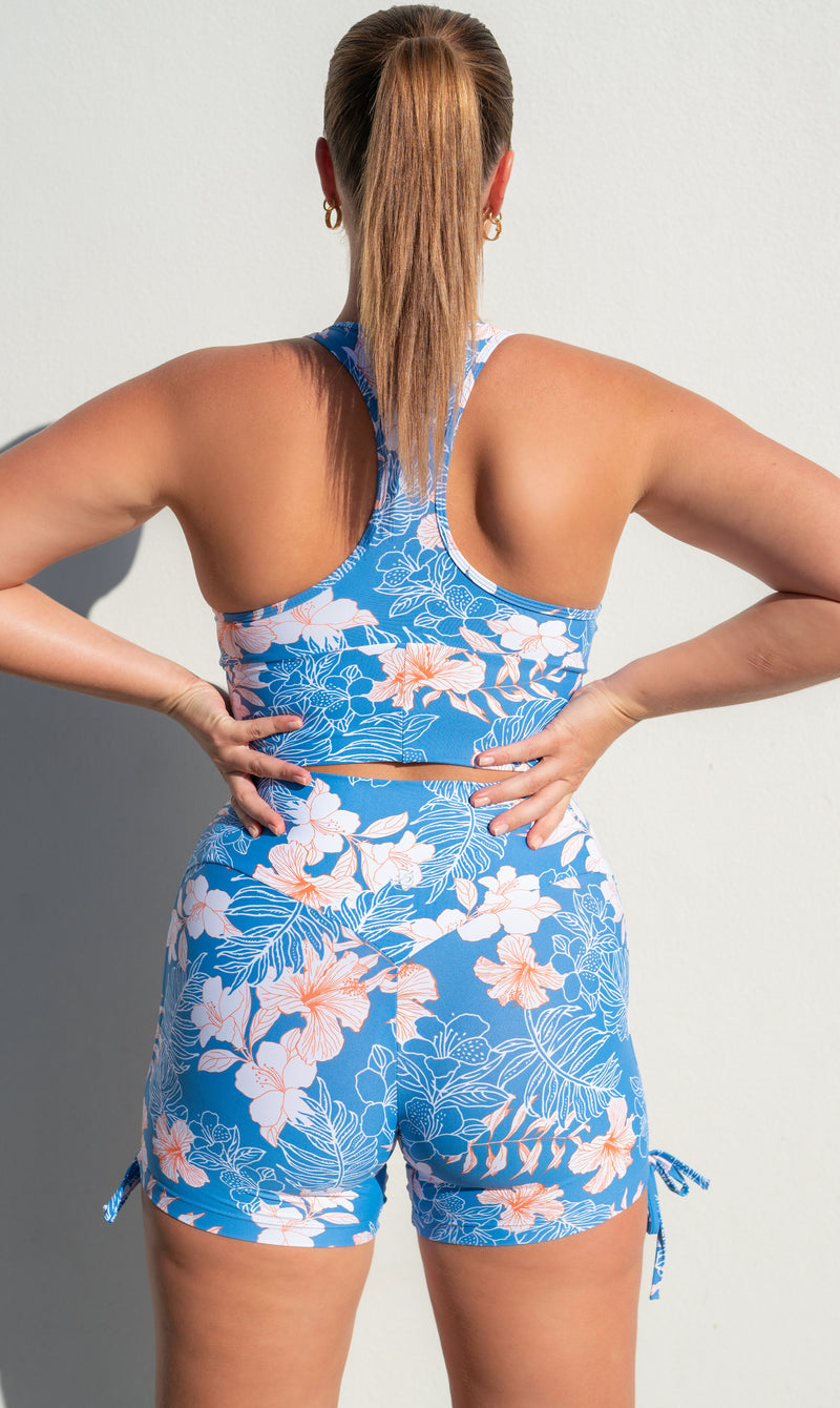 Rear view: Girl in blue, white & pink hibiscus print racer back bra & matching shorts