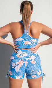 Rear view: Girl in blue, white and pink hibiscus flower print bootie shorts with ties, and matching racer back bra top