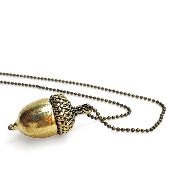 laying down view of peters kiss gold-toned necklace adorned with peter pans acorn