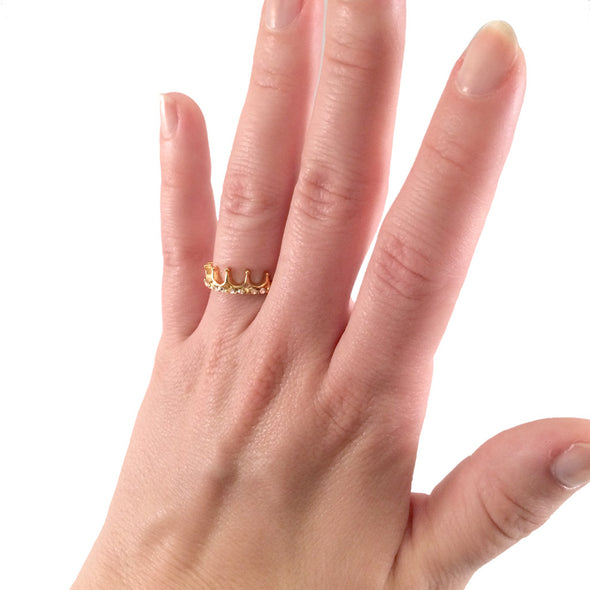 gold toned princess ring with white rhinestones on female model hand