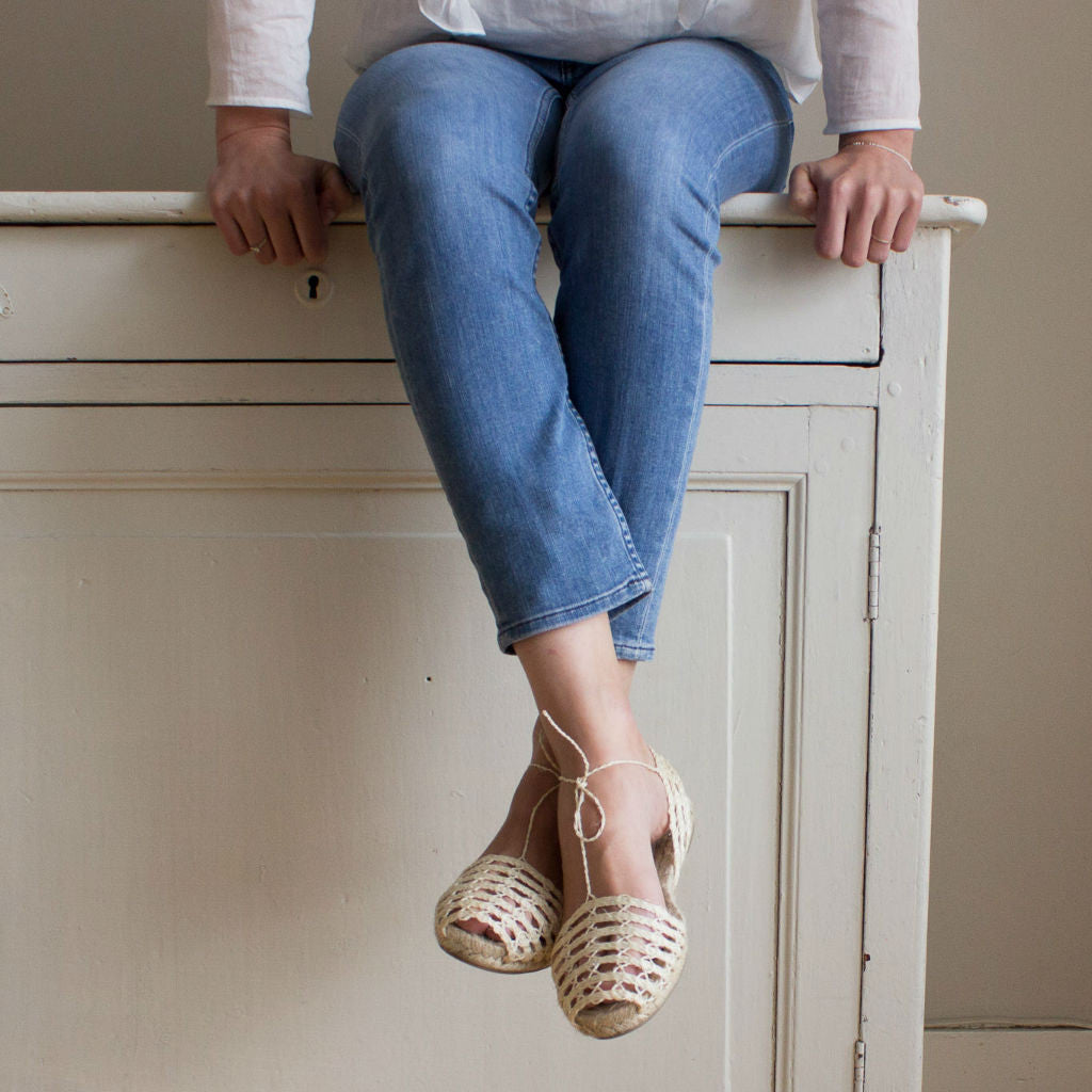 Model sitting on a chest with drawers wearing ibizan espadrilles