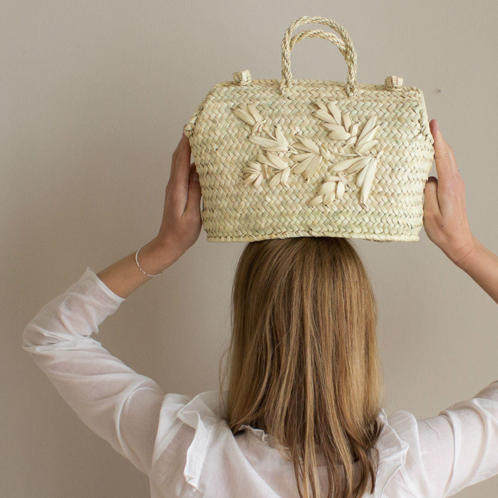 Model holding a palm leaf handbag by Sabellar over her head