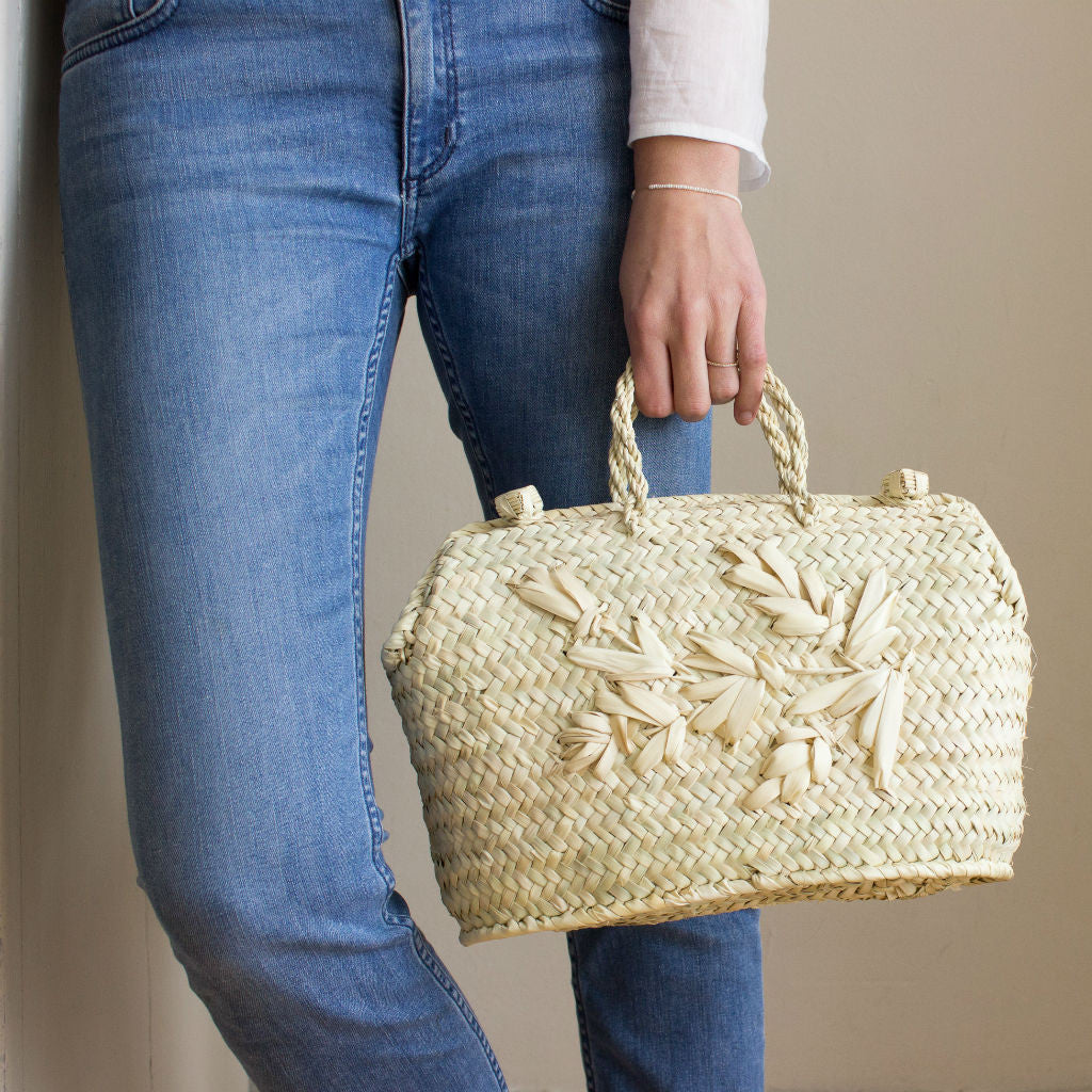 Model holding a handmade palm leaf handbag