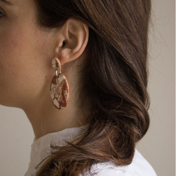 Model with Neriage ceramic earrings, made of red and white clay and silver. Photo from the side | Levens & Sabellar