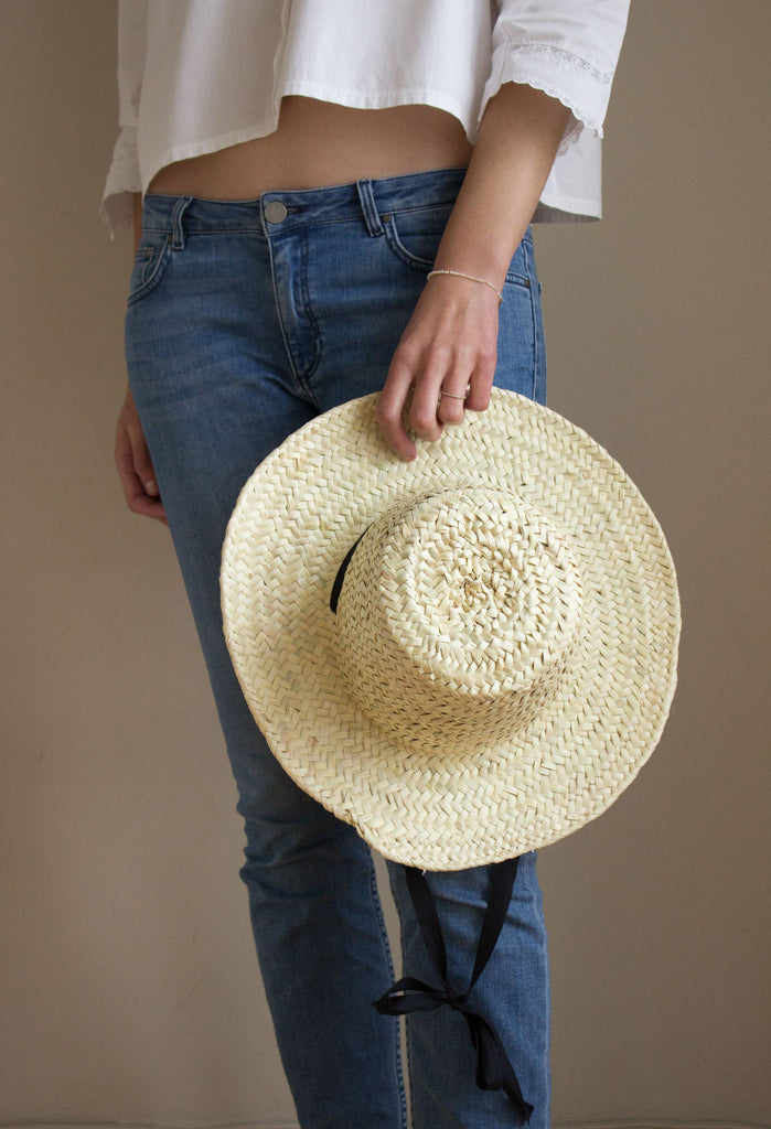 Model in jeans wearing a palm leaf hat by Sabellar