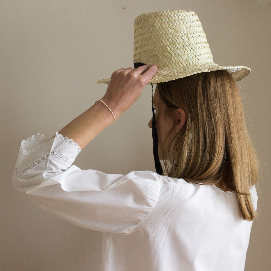 Model putting on a palm leaf hat by Sabellar