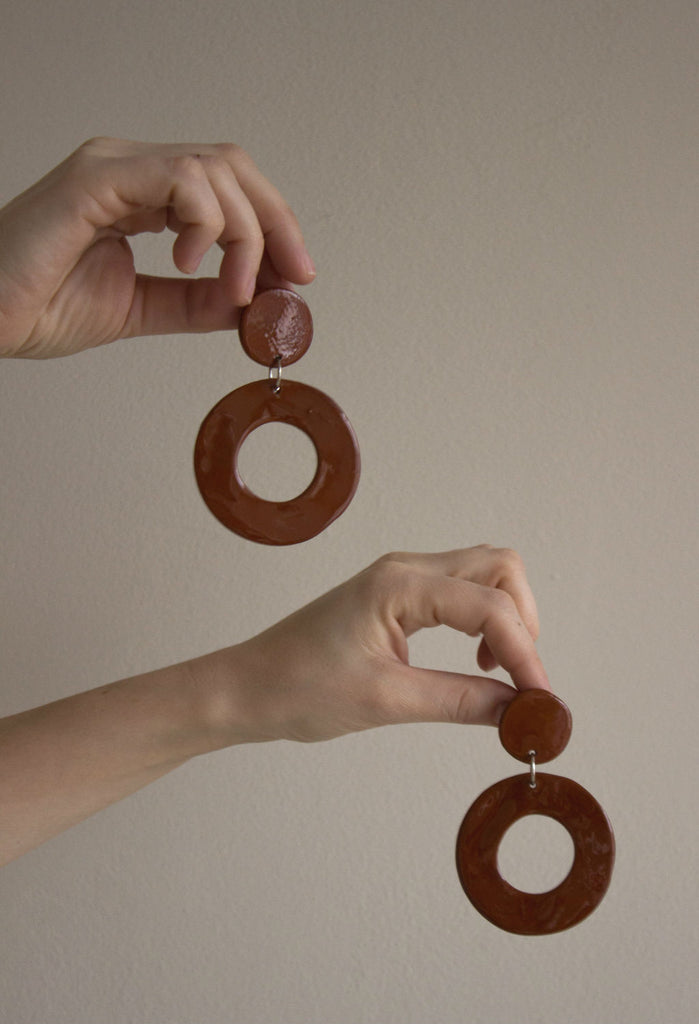 Model holding a pair of our Terracotta earrings, made of clay