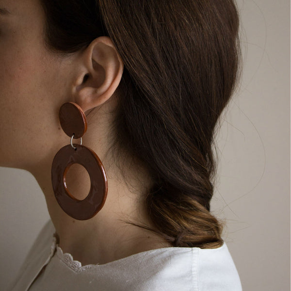 Model with Terracotta earrings. From the side. Made of clay.