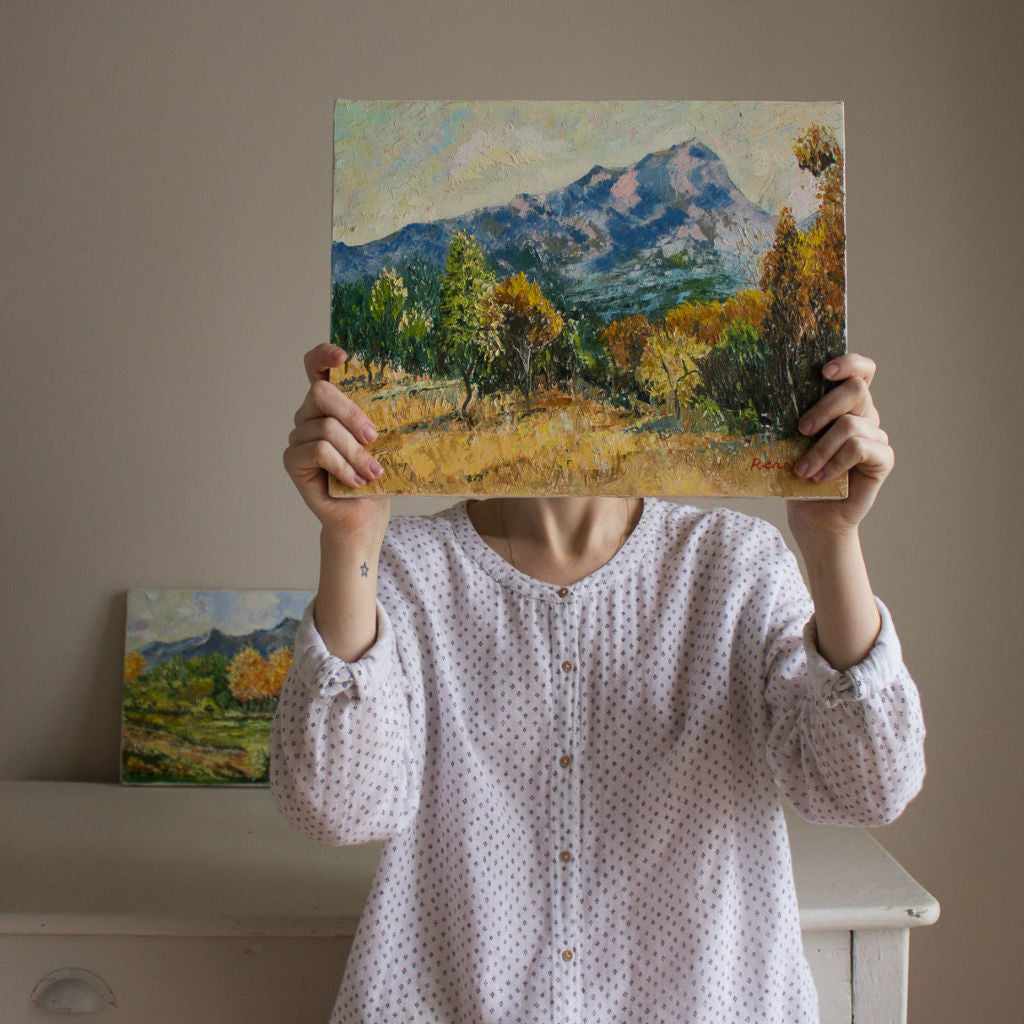 Model holding a frameless painting. Traditional Majorcan landscape, oil on canvas, dated late 20th century