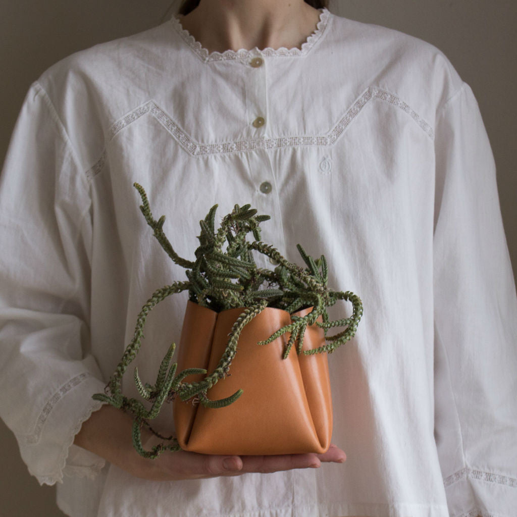 Model in an vintage blouse holding a tanned leather pot with a cactus