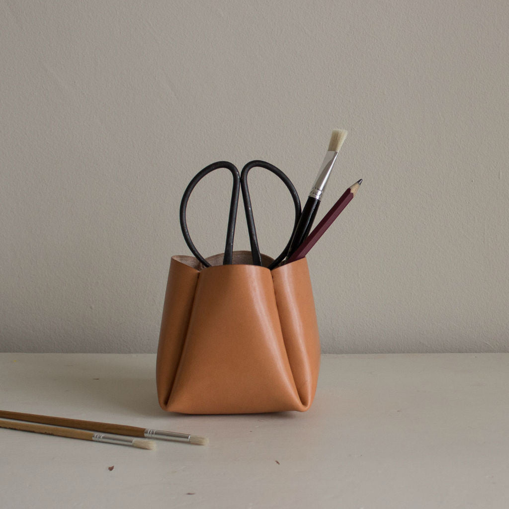 Tanned leather pot with scissors, brushes and pencils