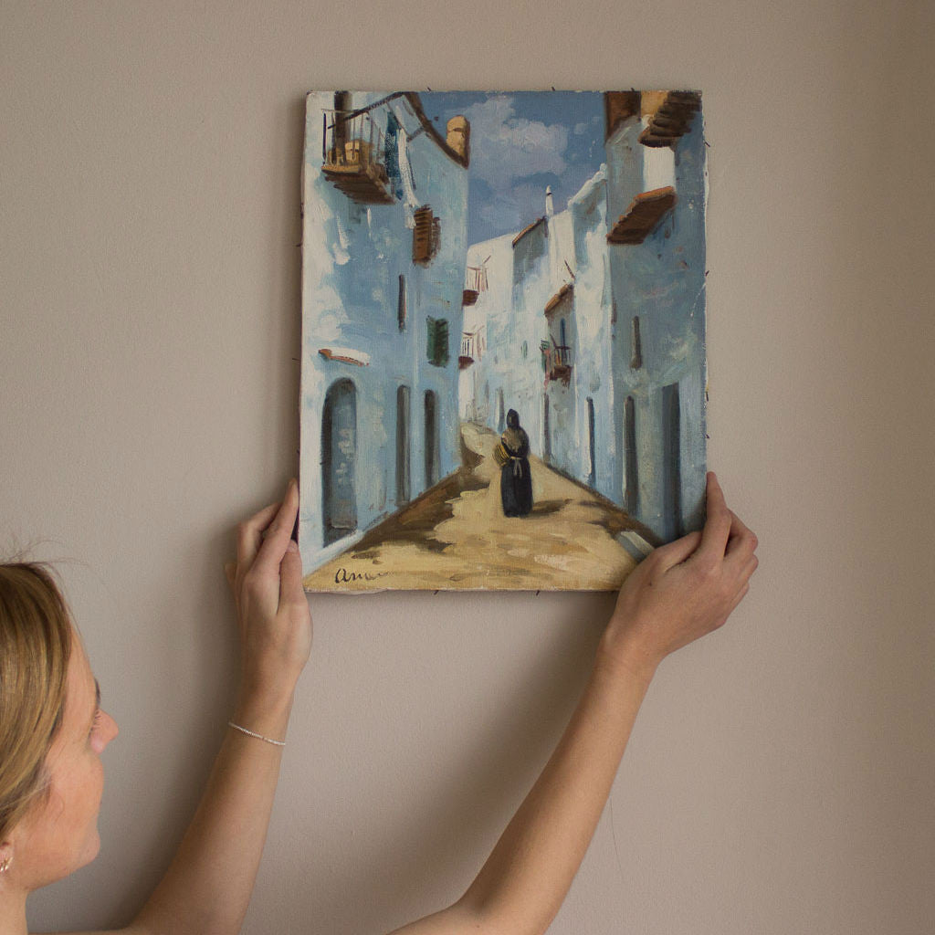 Model holds a frameless painting of a woman in a traditional local dress walking through a street of a village in Ibiza