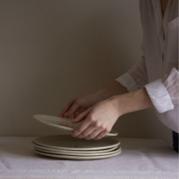 Several clay plates, coated with ashes from local pines. Model in a white cotton blouse. Handmade in Mallorca.