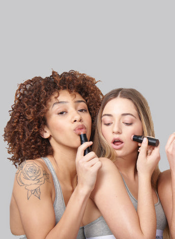 4 Nudestix models holding Nudies All Over Face Color makeup sticks