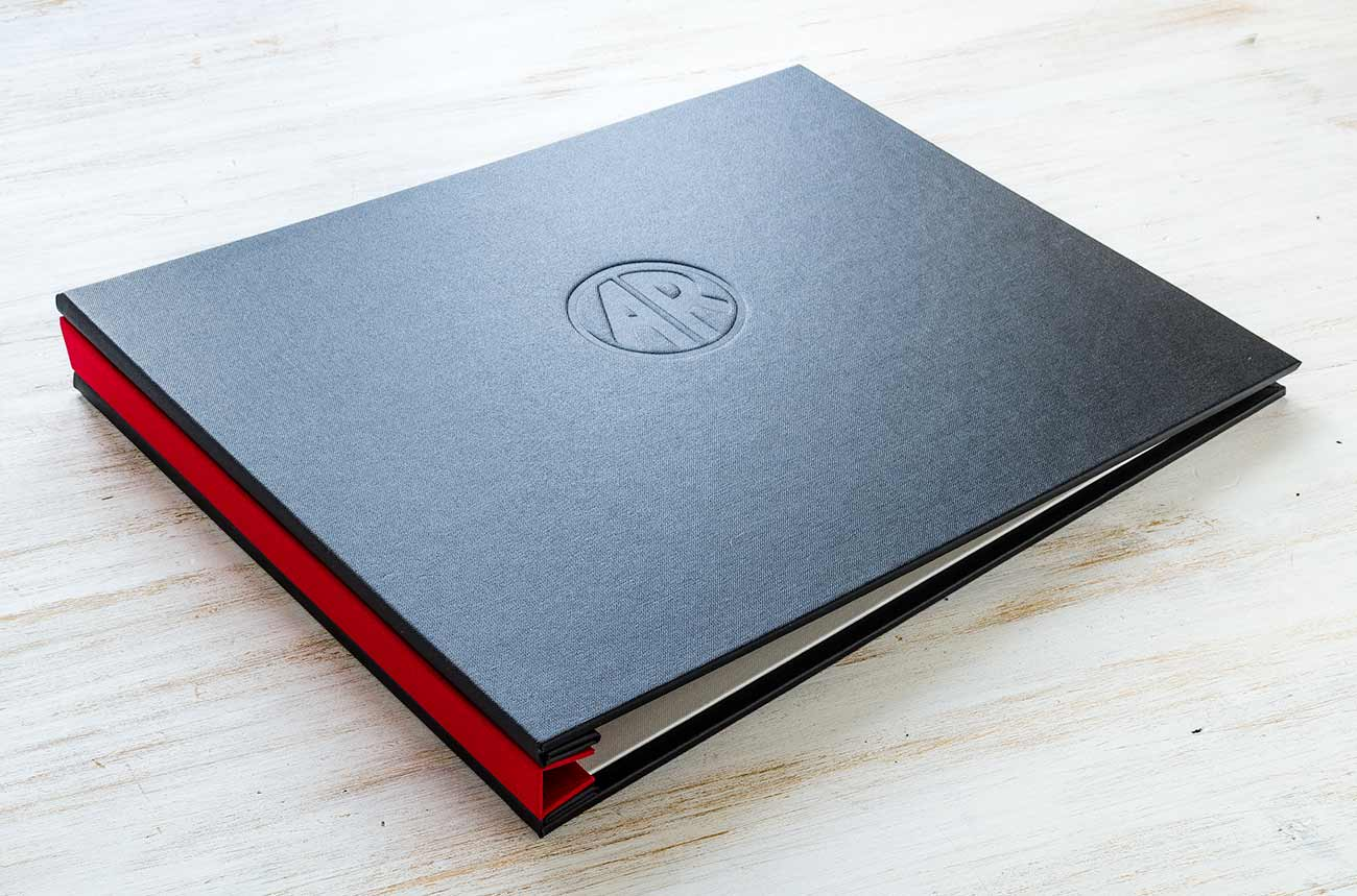 Photographers Presentation Portfolio Book - Outer Cover in Charcoal Buckram with Blind Deboss Personalisation. Spine Cover in Alton Red, Inner Cover in Pearl Buckram