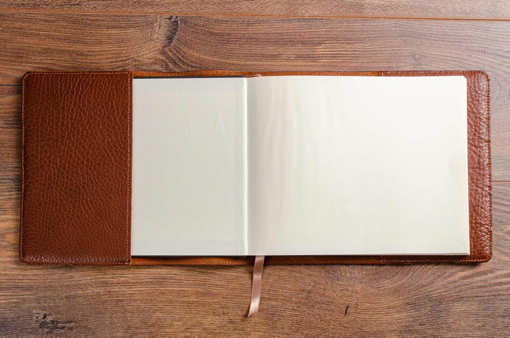 The hardcover book with its front cover within the custom made leather book jacket