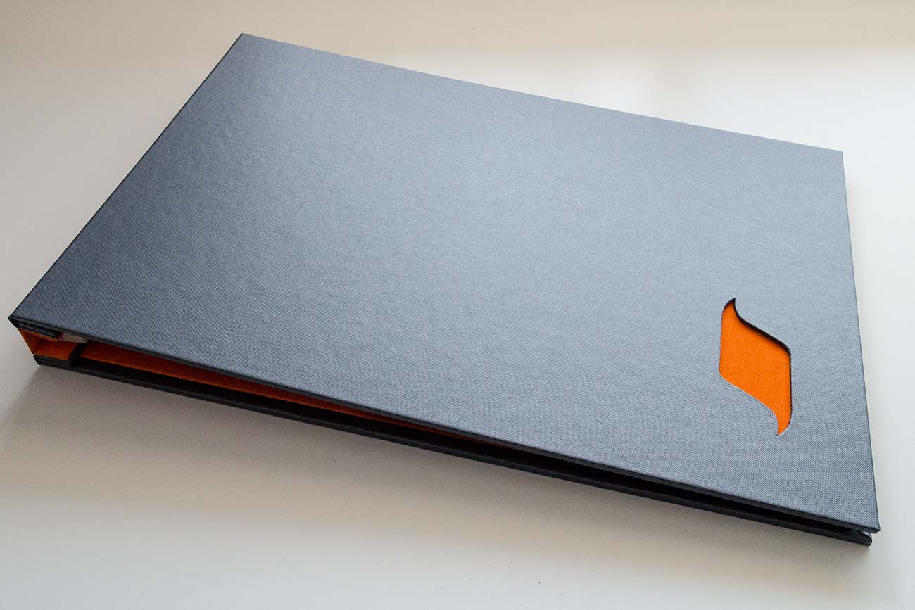 Custom portfolio book in charcoal buckram cover with cut out window with solo orange book cloth inner covers