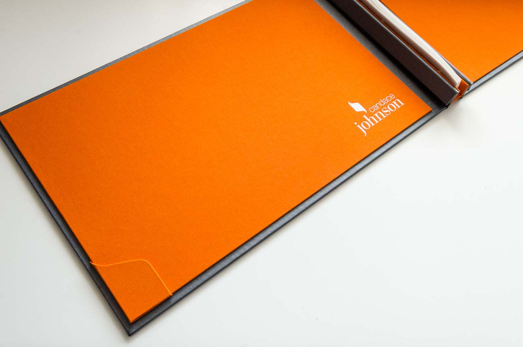 The branding form the front cover has been taken over to the inside covers with a custom business card holder and white foiled personalisation on the solo orange inner cover
