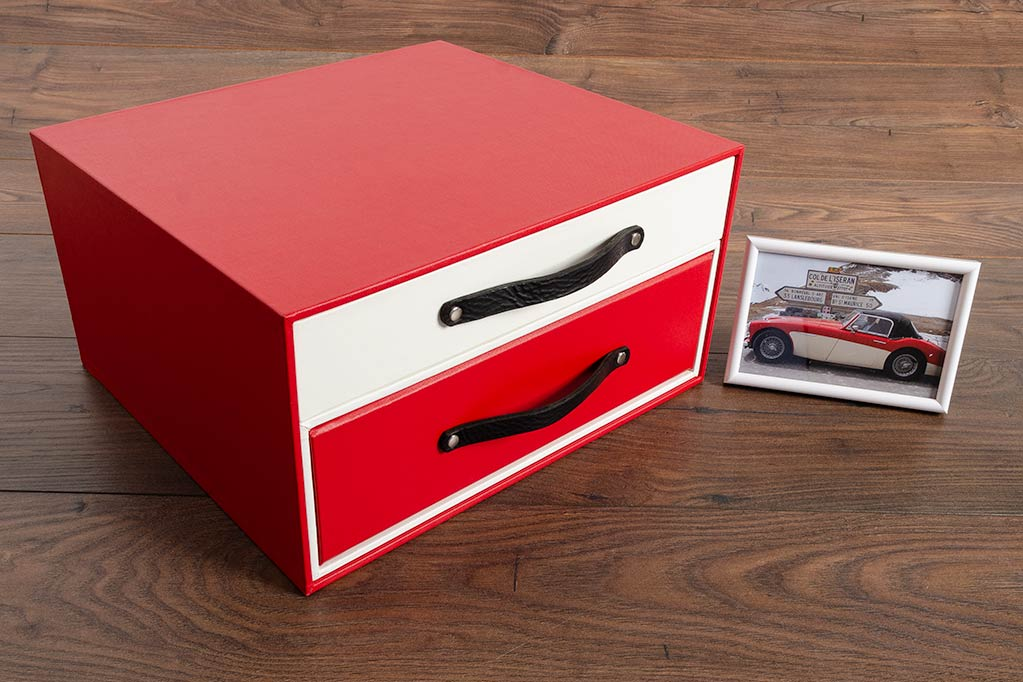 Specially commissioned box with drawer in white and binder in red. The colours match the Austin Healey car that box contains the history and restoration of