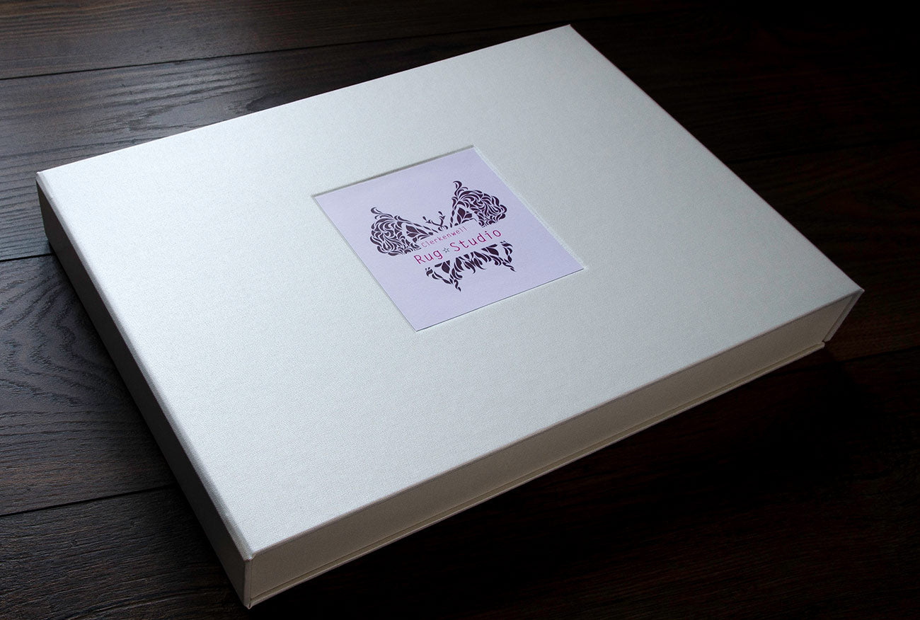Custom sized half clam shell presentation box in Pearl Buckram with a recessed space in the cover for a printed card