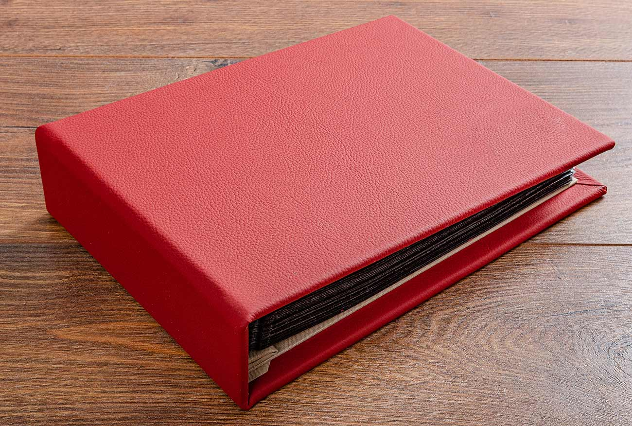 A5 sized red leather photo album for a classic car restoration. The leather matched the cars interior and the cover was gold foiled with cars make and details