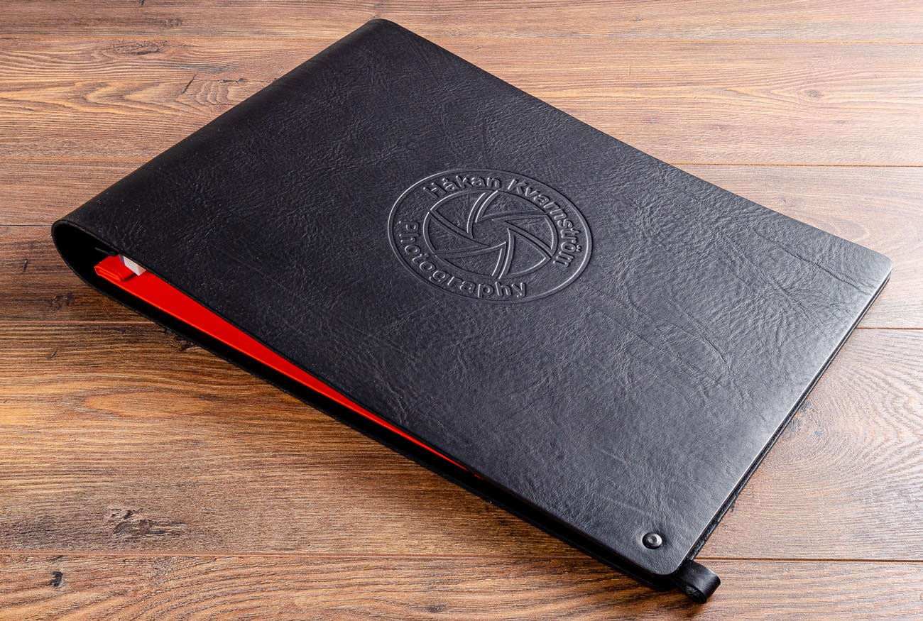 A3 portfolio book in 3.5mm black leather with a tangerine orange inner cover and blind embossed personalisation