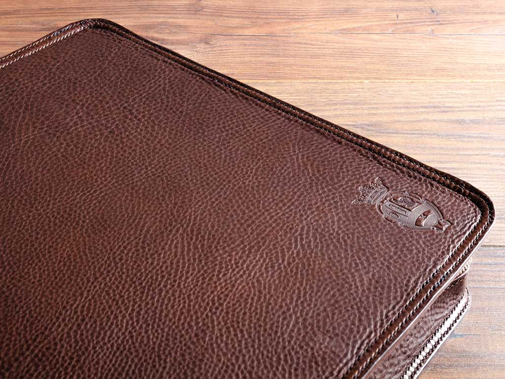 embossed logo on the cove of a custom made leather document portfolio