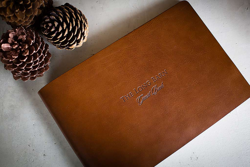 Brown leather guest book with a blind debossed personalised cover.