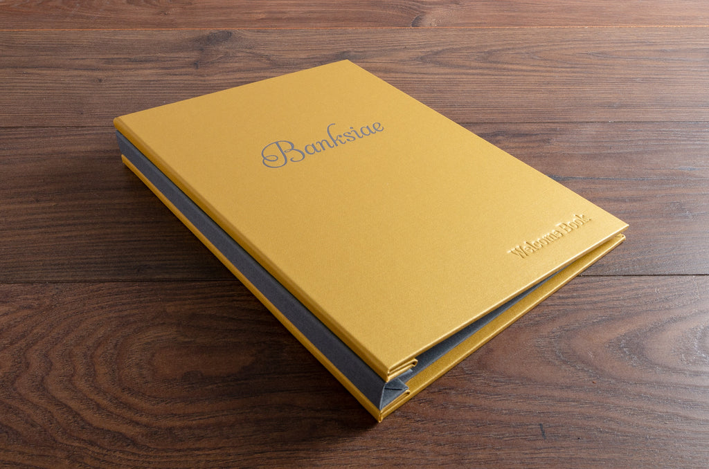 Custom made A4 guest book with a Gold buckram cover and Plate Grey spine and inner cover