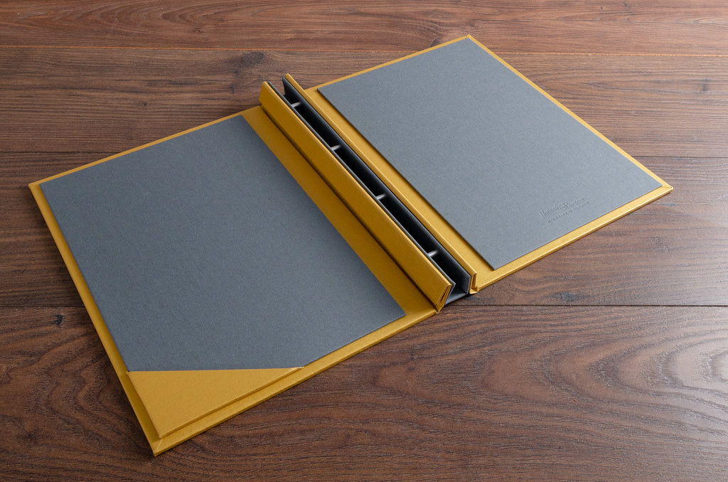 Custom made A4 guest book with a plate grey book cloth inner cover and gold buckram outer cover