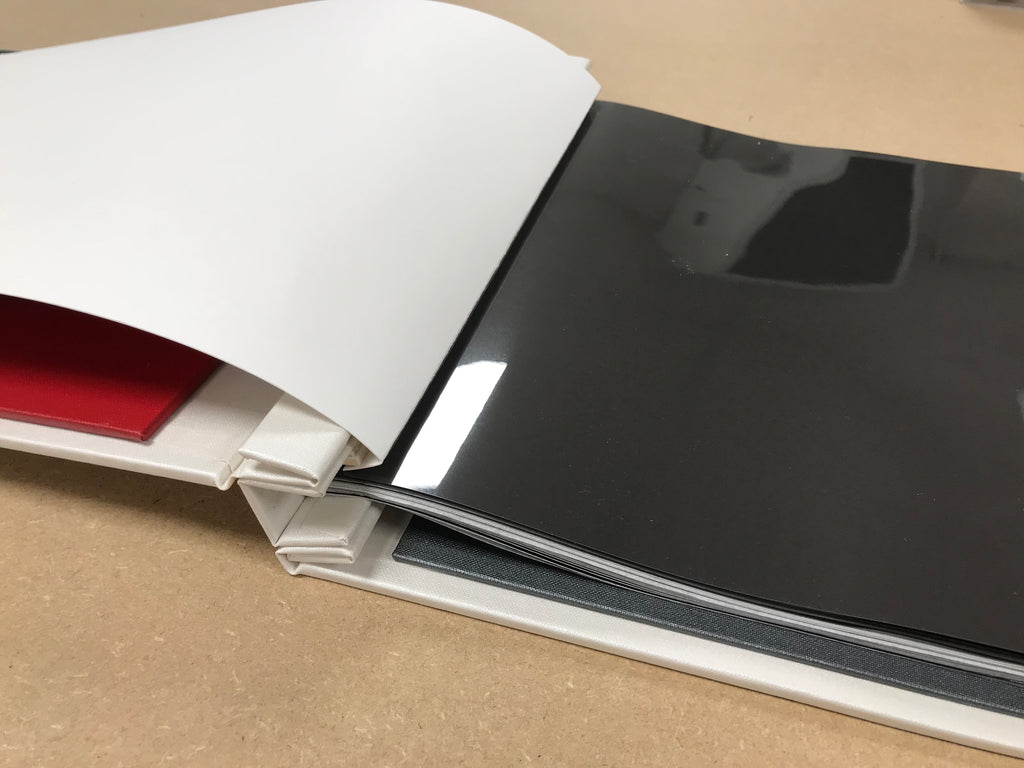 a print portfolio book with a scored page attached with hing strips
