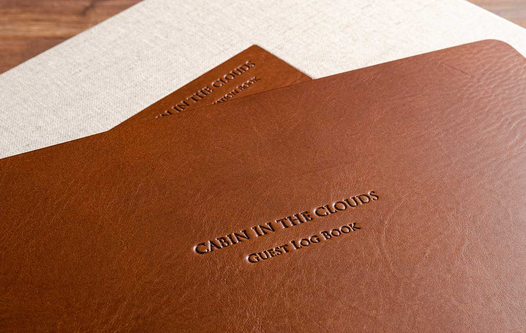 Blind embossing in leather guest book with a leather plaque in the back ground
